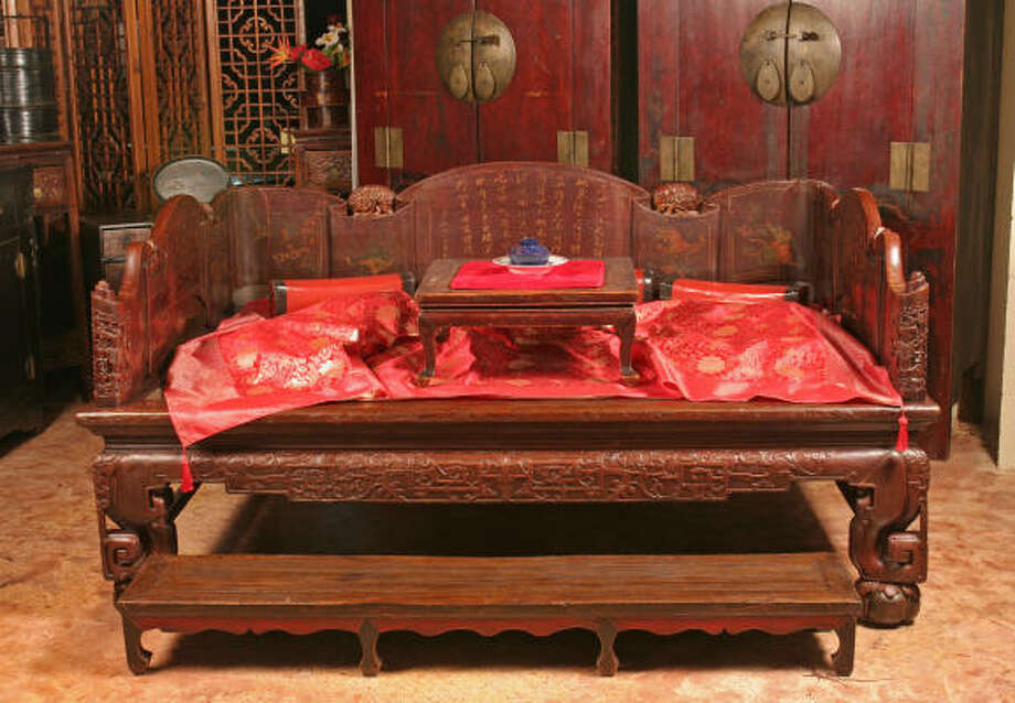An early 19th-century opium bed boasts carvings and a poem written in Chinese characters. Photo: Gary Fountain, For The Chronicle