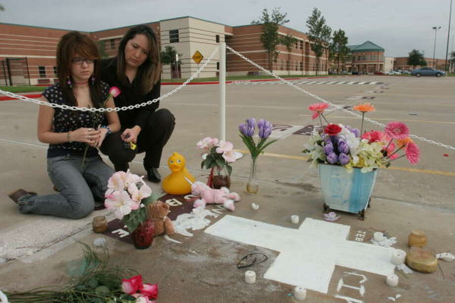 """Jacquelyn E.""""Dubadee"""" Endresen, 17, a senior at Cinco Ranch High School, was killed in a high-speed vehicle accident in late July on Katy-Flewellen Road.  From left, Alexandra Simons, 16, a junior at the school, and her mother, Kathy Simons, 41, kneel beside the student tribute to Jacquelyn in her reserved parking place in the school parking lot. Photo: Suzanne Rehak, For The Chronicle"""