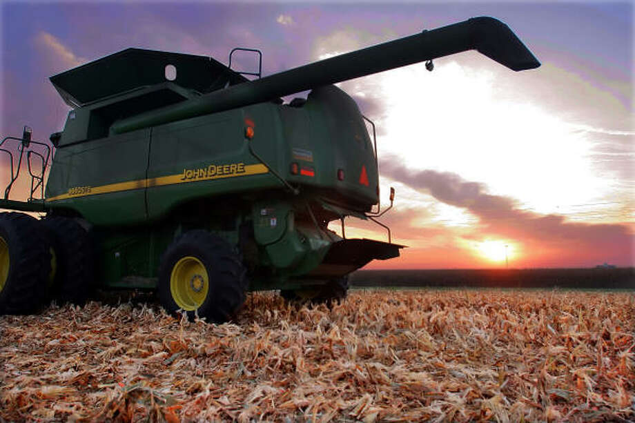 The sun rises over a combine parked on a freshly harvested cornfield near Ashland, Ill., in September. Corn prices are soaring because of the demand for ethanol, but consumers won't see higher prices in their groceries stores yet. Photo: SETH PERLMAN, AP File