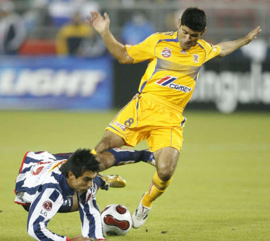 Tigres' Javier Saavedra (8), right, fouls Rayados' Leandro Gracian. Photo: Kevin Fujii, Chronicle