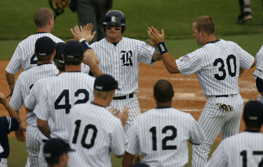 Rice's Aaron Luna, center, celebrates after scoring the winning run on a walk in the bottom of the ninth inning. Photo: Billy Smith II, CHRONICLE