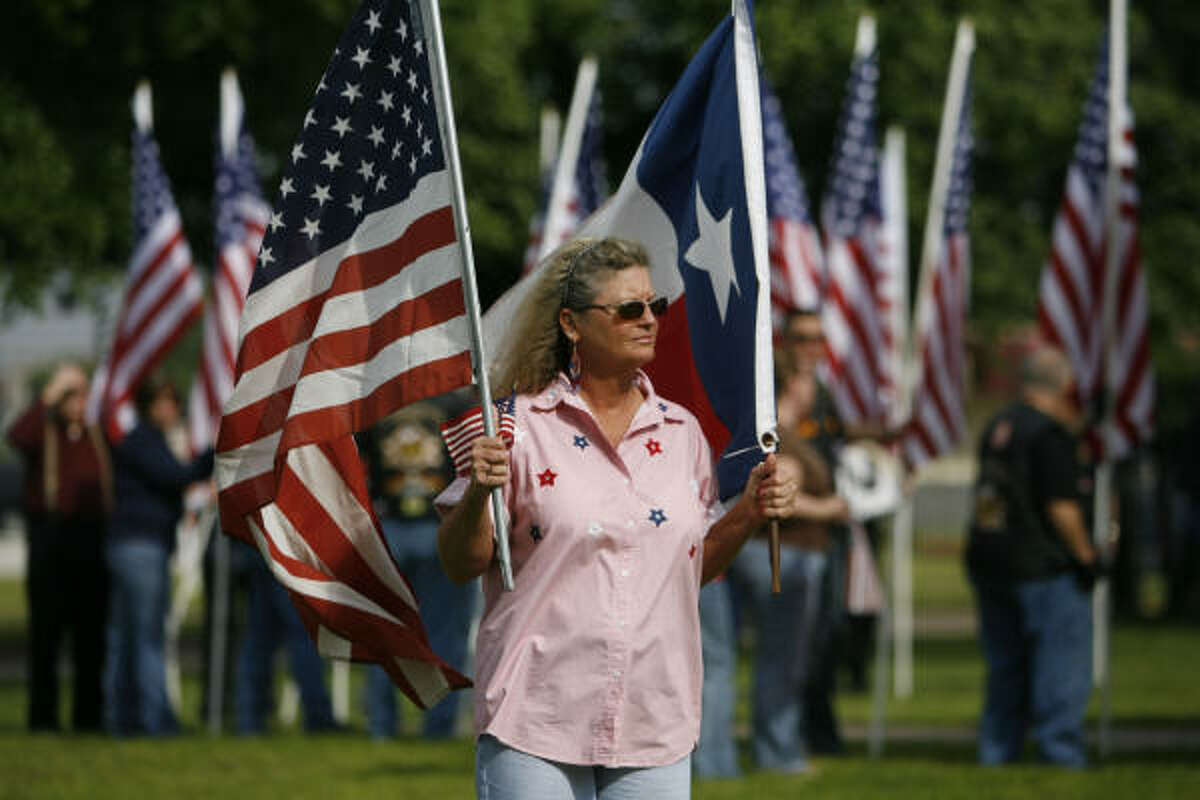 Jo Johnson lines up along Center Street this morning in Deer Park with a crowd of others holding flags.