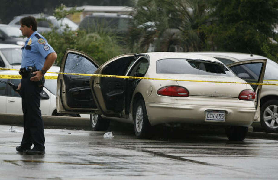 Houston police officers investigate a car with its back window blown out in the parking lot of Kelley's Restaurant and Family Dollar where a several shots were fired and cars were rammed Thursday in Houston. Photo: Karen Warren, Chronicle