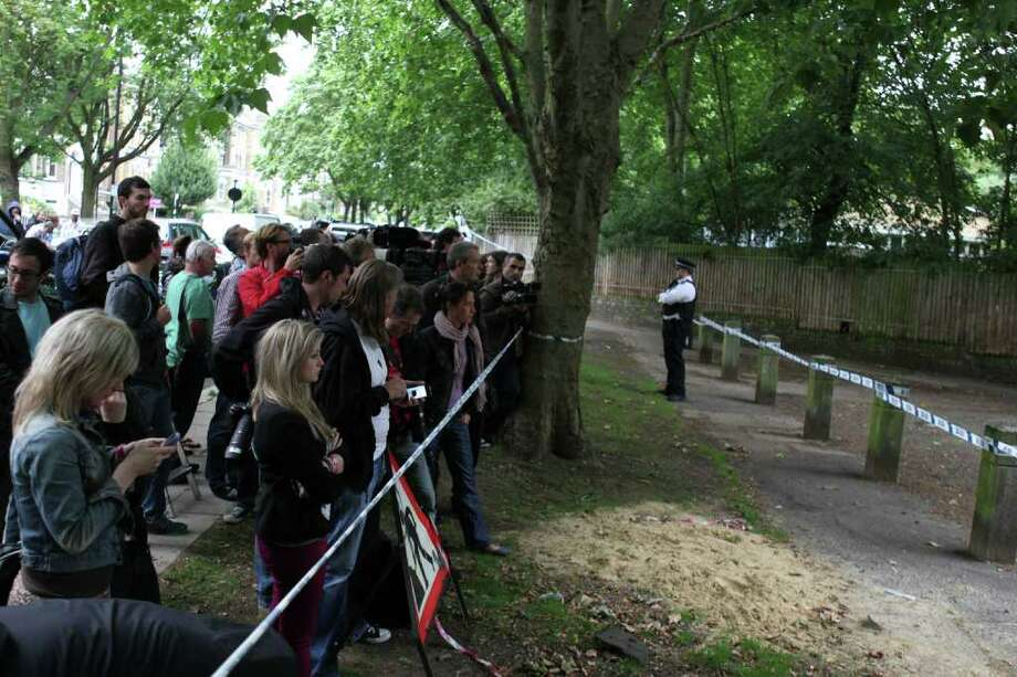 People gather behind a police cordon outside Amy Winehouse's North London Home on July 23, 2011 in London, England. Photo: Neil Mockford, Getty Images / 2011 Getty Images