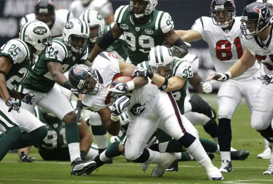 Texans running back Steve Slaton is corralled by Jets safety Jim Leonhard (36) and friends during one of his many unsuccessful rushes Sunday afternoon. Slaton and the rest of the Texans' offense totaled just 183 yards in a 24-7 loss. Photo: Brett Coomer, Chronicle