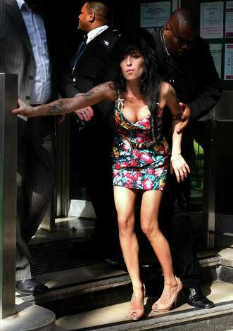 FILE - In this March 17, 2009 file photo, British singer Amy Winehouse is assisted as she leaves Westminster Magistrates Court in London, where she pleaded not guilty to a charge of common