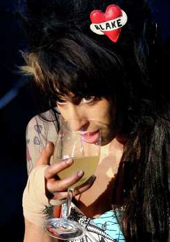 FILE - In this May 30, 2008 file photo, singer Amy Winehouse has a drink while performing to 90,000 spectators on the main stage of the Rock in Rio Lisboa music festival at the Bela Vista Park in Lisbon. Amy Winehouse, the beehived soul-jazz diva whose self-destructive habits overshadowed a distinctive musical talent, was found dead Saturday, July 23, 2011 in her London home, police said. She was 27. (AP Photo/Steven Governo, File) Photo: Steven Governo, ASSOCIATED PRESS / AP2008