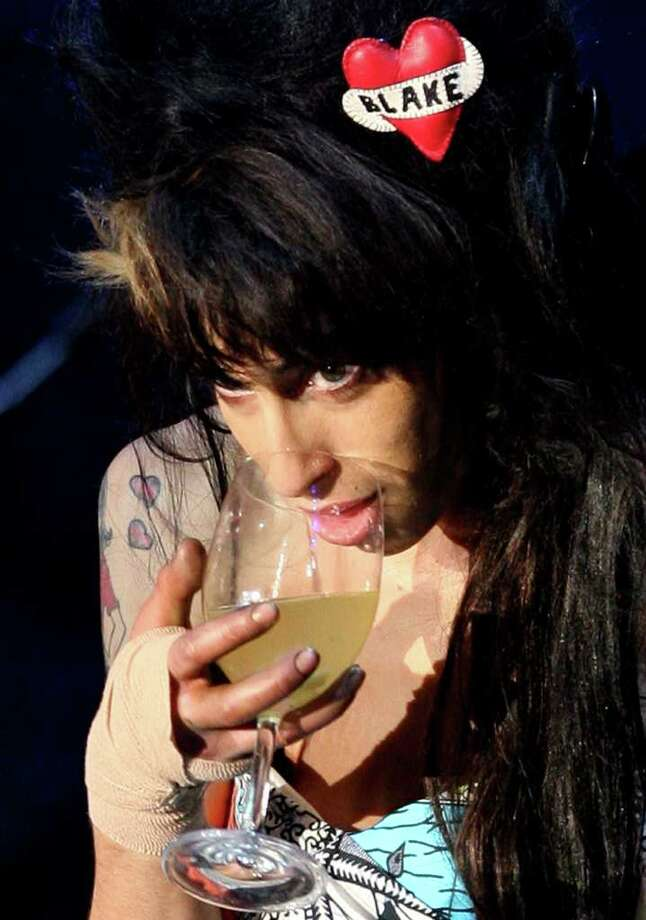 In this May 30, 2008 file photo, singer Amy Winehouse has a drink while performing to 90,000 spectators on the main stage of the Rock in Rio Lisboa music festival at the Bela Vista Park in Lisbon. Photo: Steven Governo, ASSOCIATED PRESS / AP2008
