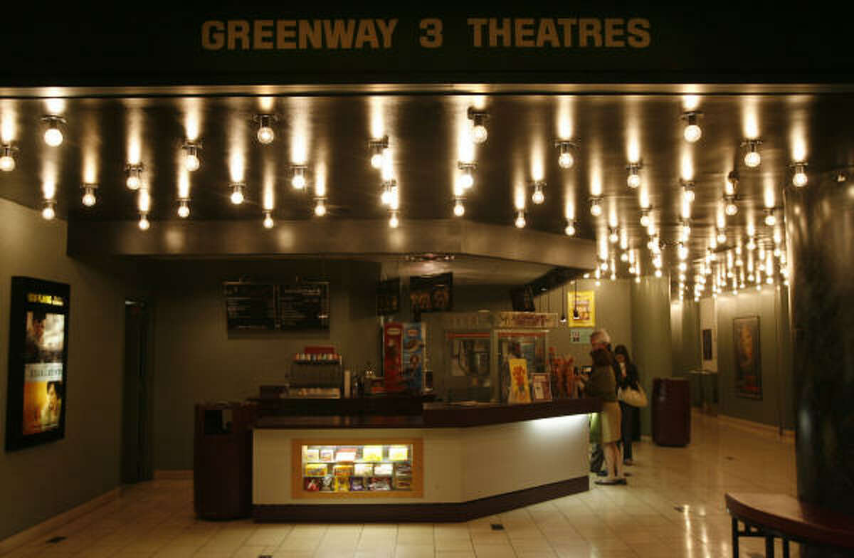 Movie patrons buy snacks at the concession stand at the Greenway Theatre on Monday in Houston. The theater will close on New Year's Eve after more than 30 years of operation.