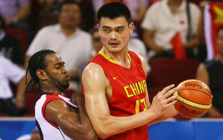 Yao Ming of China backs into Angola's Joaquim during China's 85-68 victory. Photo: Jeff Gross, Getty Images