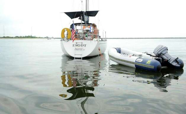 Woody Oldrin's boat, Ingot, sits in Bridgeport Harbor Saturday, July 23, 2011 off of Seaside Park for the Gathering of the Vibes festival.  Oldrin and friends camped on the boat.  This is the first year the festival has allowed off shore camping and access to the venue by boat. Photo: Autumn Driscoll / Connecticut Post Staff