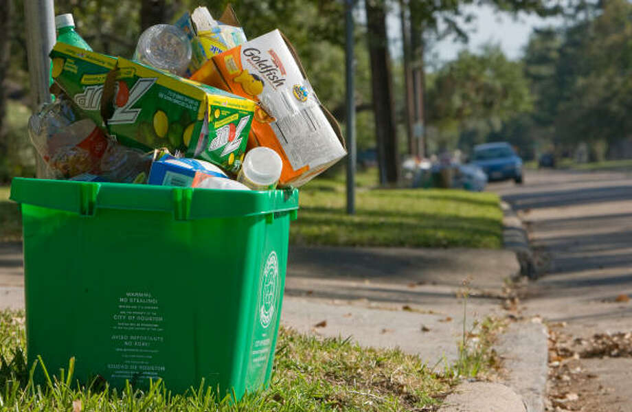 A full recycling container sits on the curb Thursday in the 4900 block of Oak Forest in northwest Houston. Photo: Steve Campbell, Chronicle