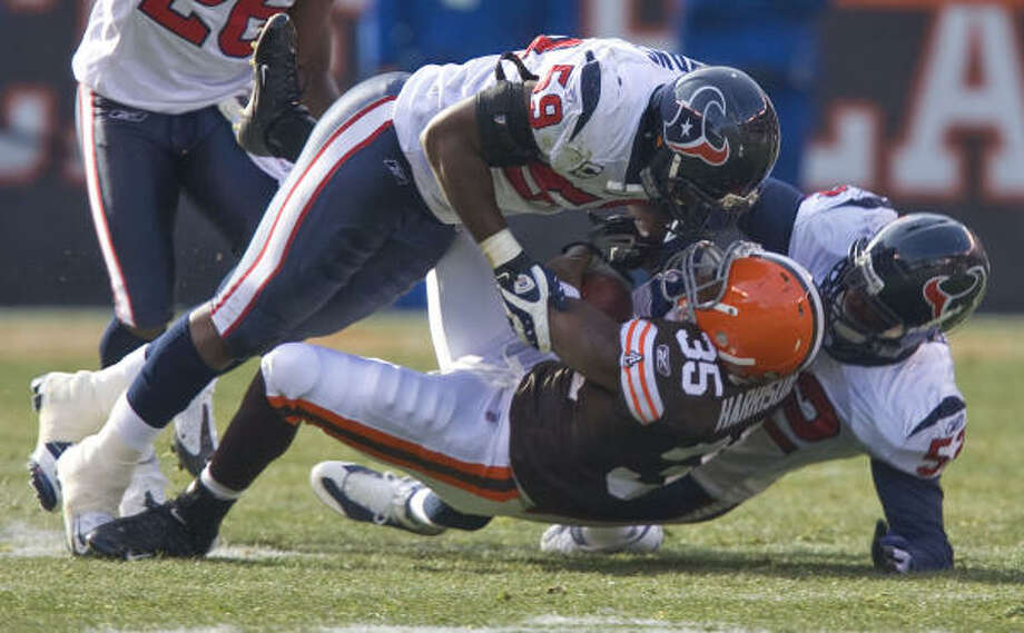 Texans defenders DeMeco Ryans, top, and Xavier Adibi combine to stop Cleveland's Jerome Harrison in the second quarter Sunday. Photo: James Nielsen, Chronicle