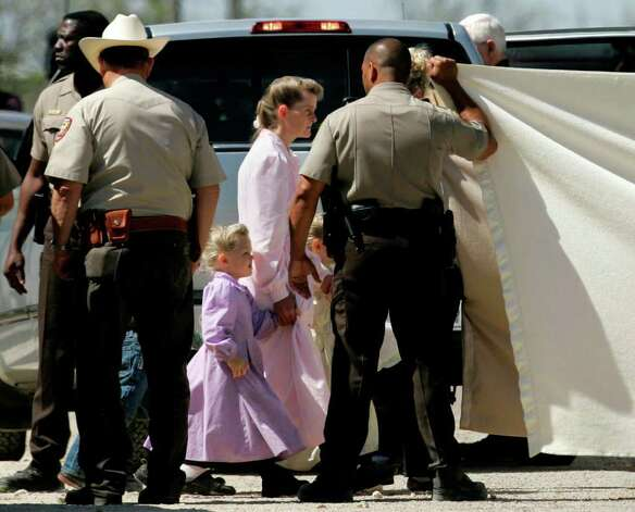 This April 6, 2008, file photo, shows members of The Fundamentalist Church of Jesus Christ of Latter-day Saints as they are assisted by law enforcement officials to board a San Angelo Independent School District bus which is being used to relocate them from Eldorado, Texas, to San Angelo, Texas. Members of the Fundamentalist Church of Jesus Christ of Latter Day Saints - a radical offshoot of mainstream Mormonism that believes polygamy is the key to heaven _ were subject of a SWAT team raid where 439 children were seized from mothers in 2008. Photo: Tony Gutierrez, STF / 2008 AP
