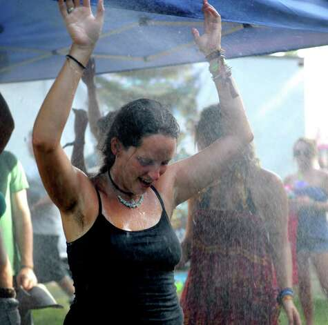 May Slater of Mansfield, PA, cools off under a spray of water during The Gathering of the Vibes on Saturday, July 23, 2011. Photo: Lindsay Niegelberg / Connecticut Post Staff