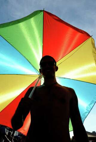Dominick Slomko of New Brunswick, NJ stands in silhouette under an umbrella during The Gathering of the Vibes on Saturday, July 23, 2011. Photo: Lindsay Niegelberg / Connecticut Post Staff