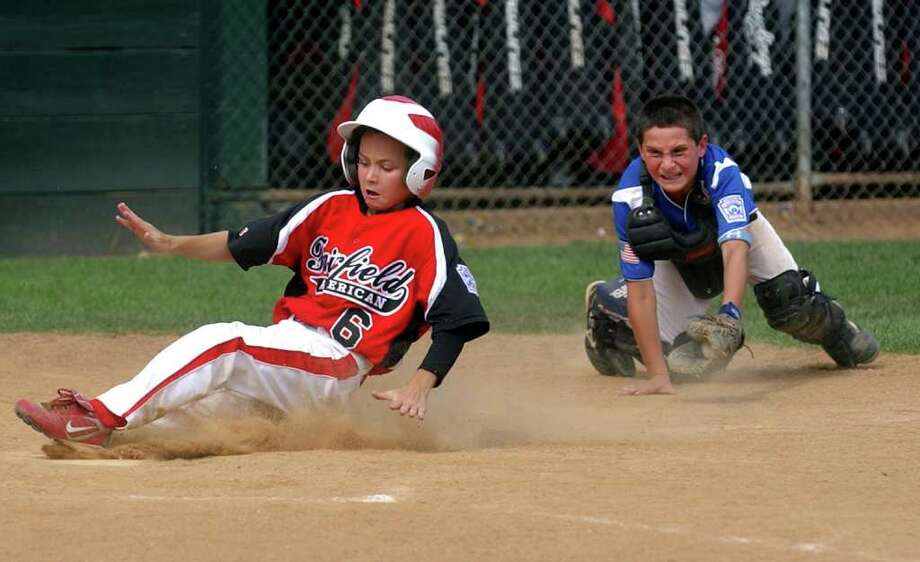 Fairfield American's #6 Connor Devaney slides safely into home plate as North Stamford's catcher Anthony Socci fails to reach him for the tag, during little league sectional baseball action at Old Tavern Park in Orange, Conn. on Saturday July 23, 2011. Photo: Christian Abraham / Connecticut Post
