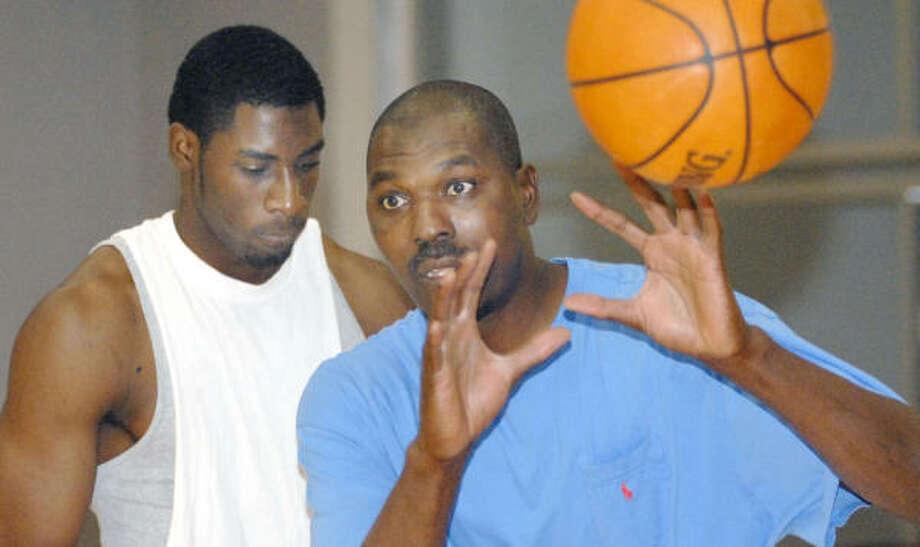 Ex-Rocket Hakeem Olajuwon, right, and SMU's Ike Ofoegbu work out at Hakeem's Big Man Camp on Thursday. Photo: TIM JOHNSON, For The CHRONICLE