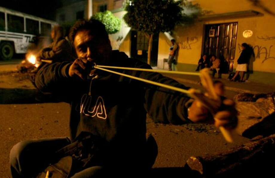 A member of the Popular Assembly of Oaxaca demonstrates a slingshot. The group is demanding the state governor's resignation. Photo: DANIEL AGUILAR, REUTERS