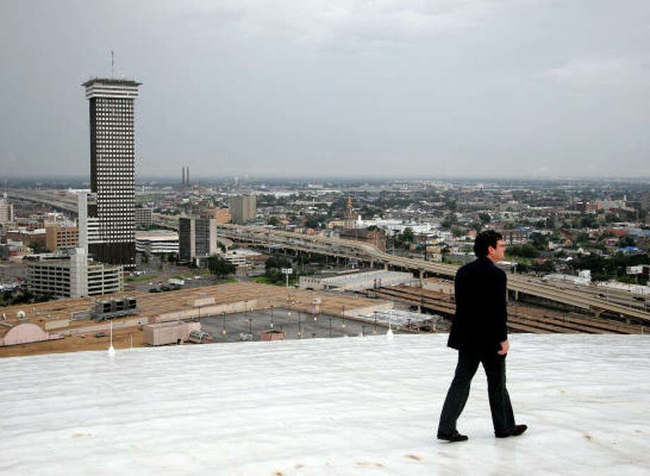 Architect Trey Trahan walks on the roof of the Louisiana Superdome in New Orleans in September. The city's employment level is decades behind what it was when Hurricane Katrina hit. Photo: ALEX BRANDON, AP