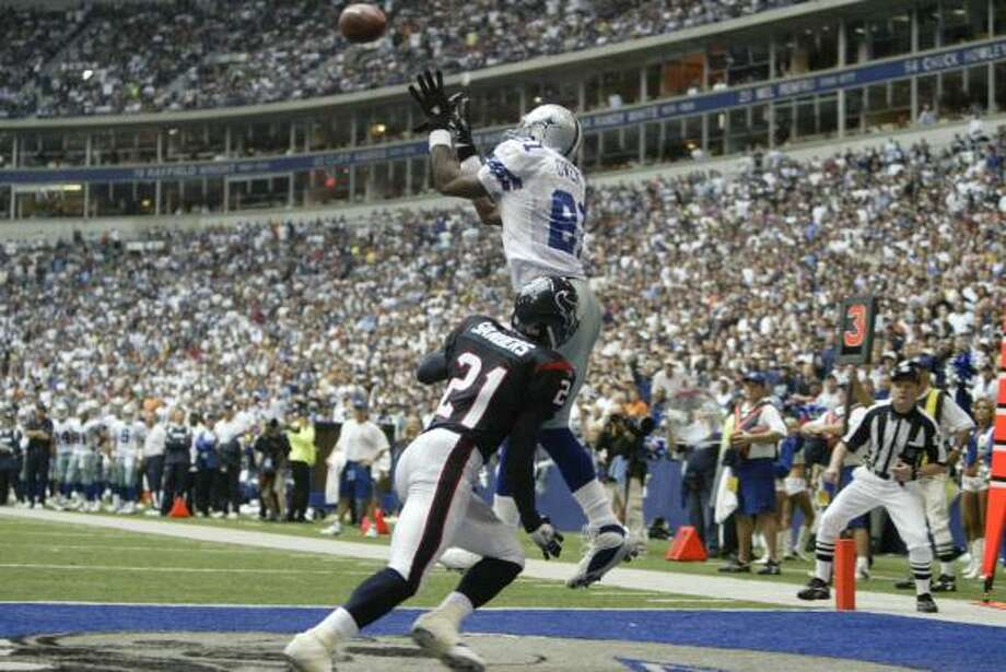 Cowboys receiver Terrell Owens hauls in a touchdown over Texans cornerback Lewis Sanders. It was his first of three touchdowns. Photo: Billy Smith II, CHRONICLE
