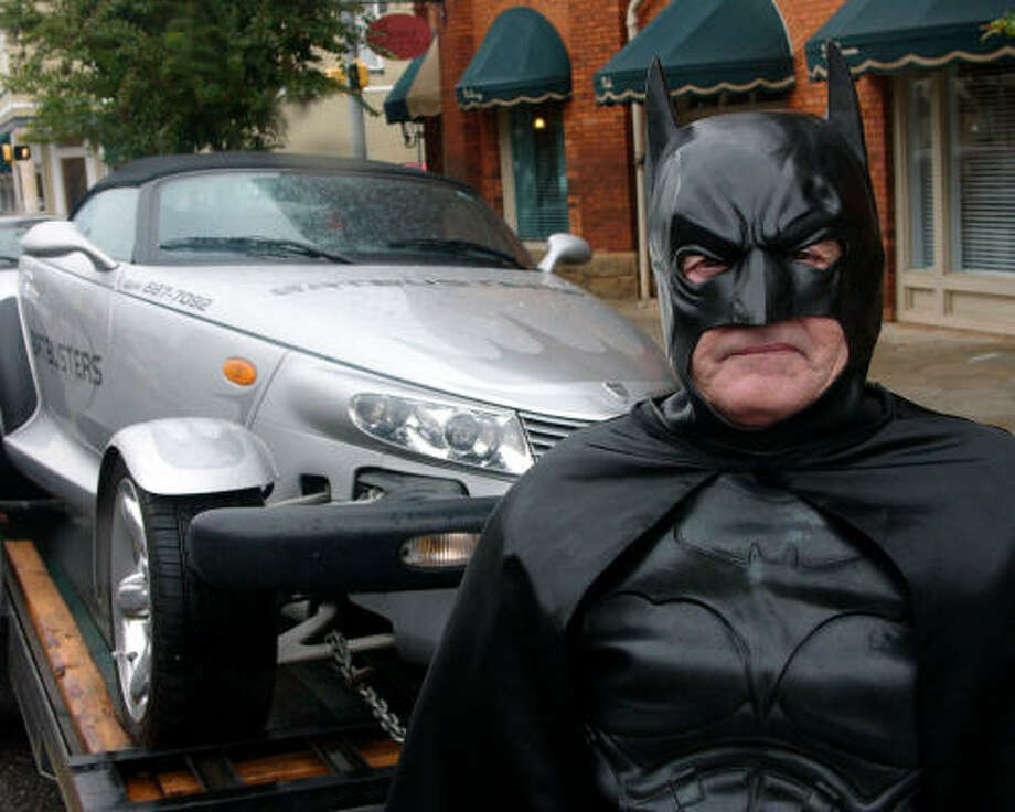 George Perkins, owner of a bat-removal company in Americus, Ga., often appears in public as Batman and drives his own Batmobile, a retro-styled Chrysler Prowler. Photo: ELLIOTT MINOR, AP
