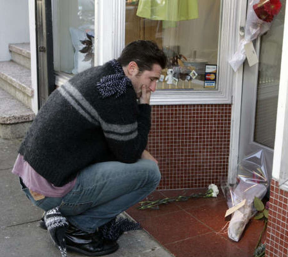 Peter Helmenstine grieves at a store owned by the Kim family Wednesday in San Francisco. After the family's car got stuck on a remote Oregon road, James Kim, 35, ventured off on foot to find help. Photo: Ben Margot, AP