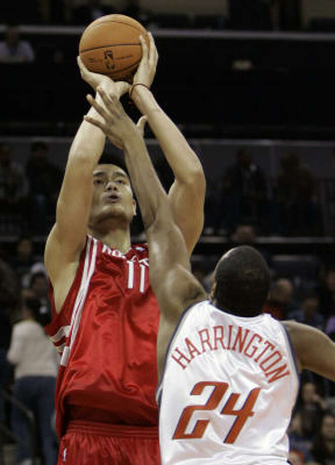 Yao Ming launches a shot. He had 21 points on Friday and has gone over 20 in 14 of his last 16 games. Photo: CHUCK BURTON, AP