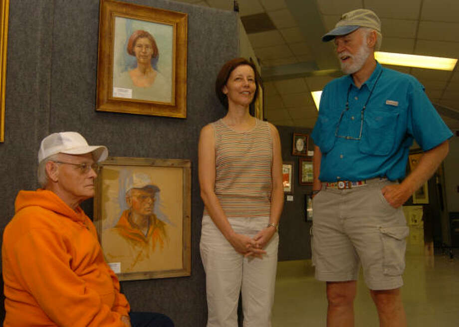 Joe Hendrix, left, and Kerry Cawthorne visit with Woodlands artist Fred Hulser at The Woodlands Community Center. Hulser painted portraits of both Hendrix and Cawthorne, which hang on the wall behind them. Photo: David Hopper, For The Chronicle