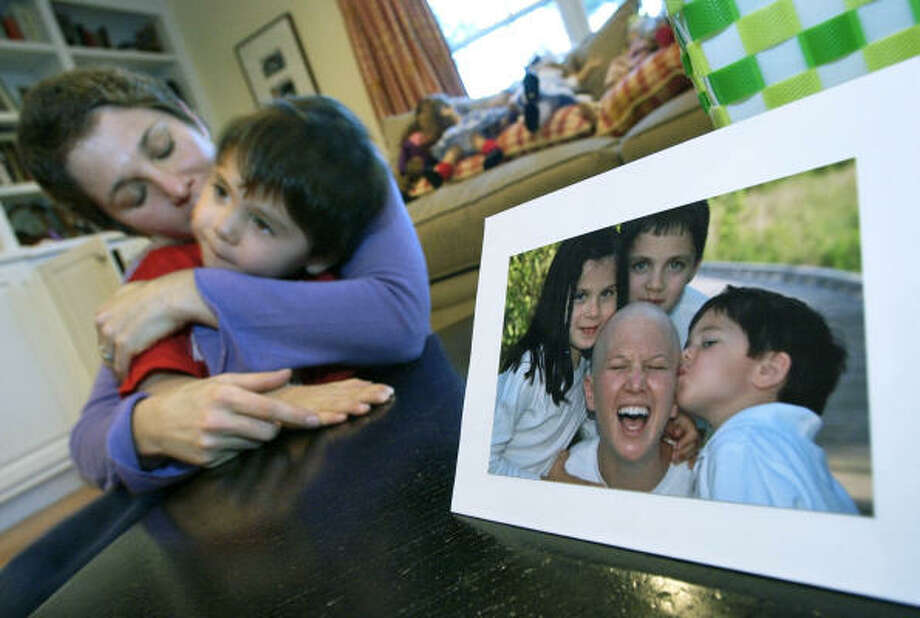 """Breast cancer survivor Robin Khadduri, at home Saturday with her son, Leo, 4, is undergoing """"chemopause"""" in one of three large experiments now under way to test ovary suppression to fight cancer. At right is a photo of Khadduri with her three children while she was in chemotherapy treatment. Photo: LISA POOLE, AP"""