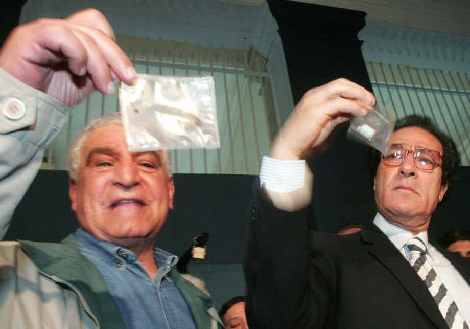 Zahi Hawass, Egypt's antiquities chief, left, and Egyptian Culture Minister Farouk Hosni view 3,200-year-old samples of hair, linen bandages and resin used in the mummification of pharaoh Ramses II. Photo: CRIS BOURONCLE, AFP/Getty Images