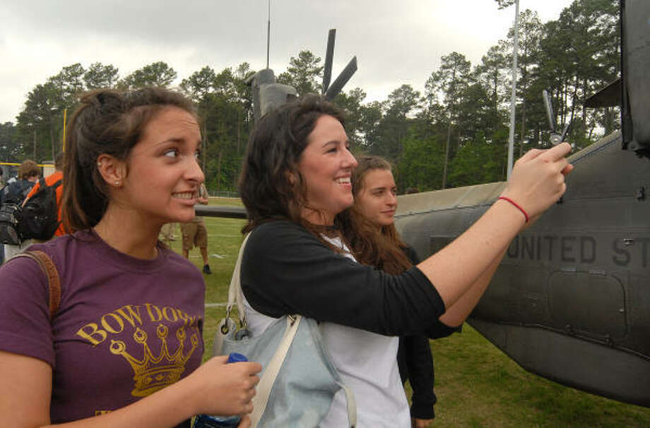 Conroe High School physics students Jillian Lambert, left, Chera Smith and Ashley Girsson, take pictures of a U.S. Army Apache helicopter on the subvarsity field at Conroe High School. Photo: David Hopper, For The Chronicle