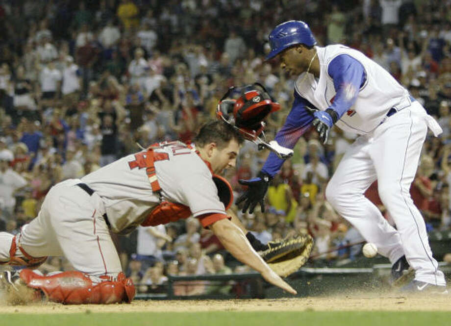The Rangers' Kenny Lofton, right, knocks the ball loose from Angels catcher Mike Napoli as Lofton scores on a RBI-double by teammate Michael Young. Photo: Matt Slocum, AP