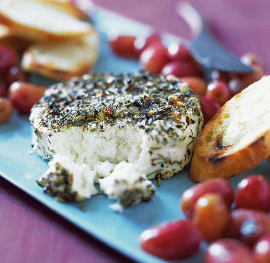 UPSCALING A CLASSIC:Warm goat cheese may be scooped or spread onto baguette slices in this recipe for Grilled Chèvre With Popped Grapes. Photo: Chronicle Books