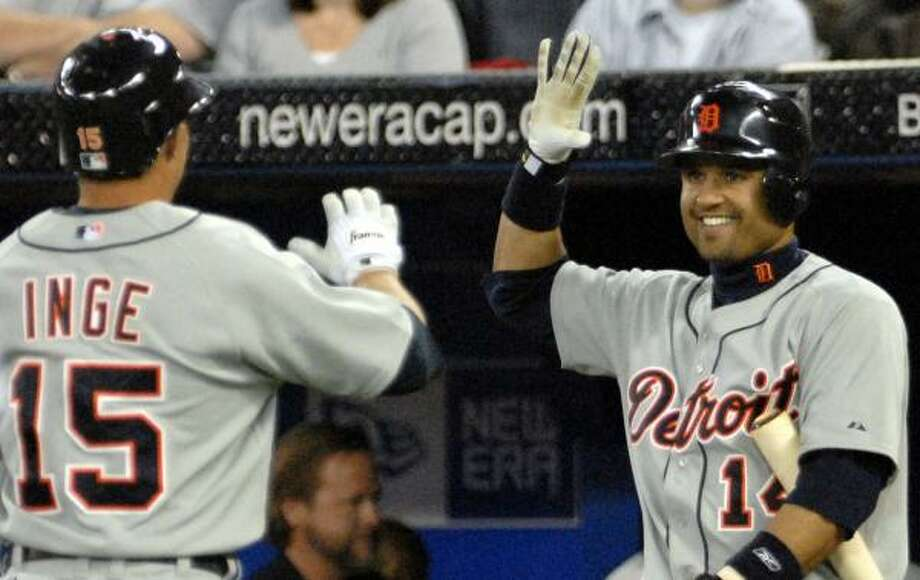 Brandon Inge's second and third hits of the season included a home run to help beat the Blue Jays on Thursday, much to the delight of beaming Tigers teammate Placido Polanco, right. Photo: AARON HARRIS, ASSOCIATED PRESS