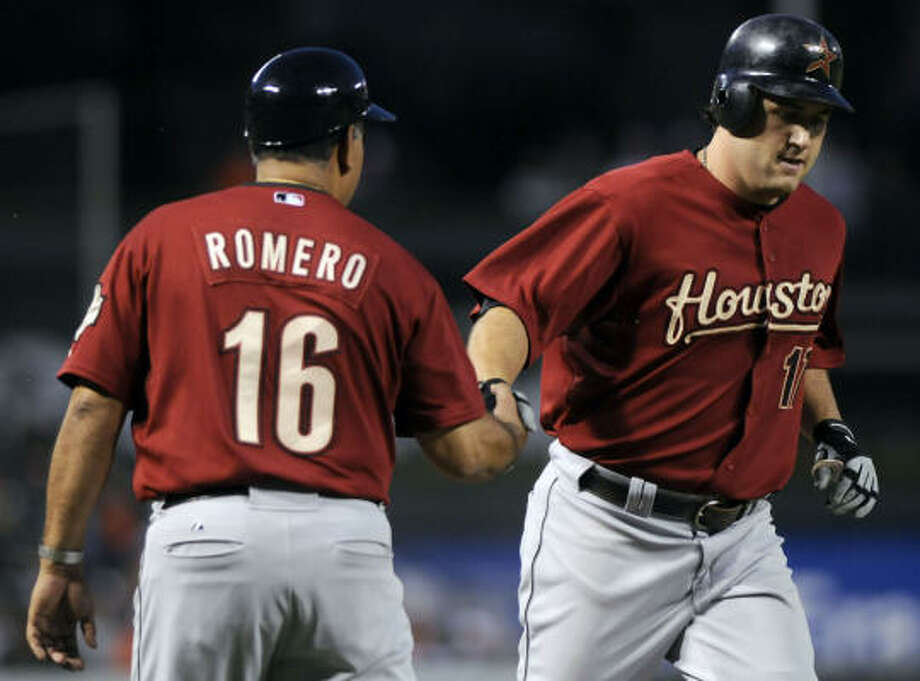 Astros' Lance Berkman, right, slaps hands with third base coach Ed Romero after Berkman's solo home run in the seventh inning against the Baltimore Orioles on Wednesday. Baltimore won 2-1 in 10 innings. Photo: Steve Ruark, AP