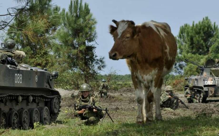 Russian troops take up positions on farmland during an operation outside of the Black Sea port of Poti, Georgia, on Thursday. Russian forces Wednesday targeted three Georgian boats in Poti. Photo: BELA SZANDELSKY, ASSOCIATED PRESS