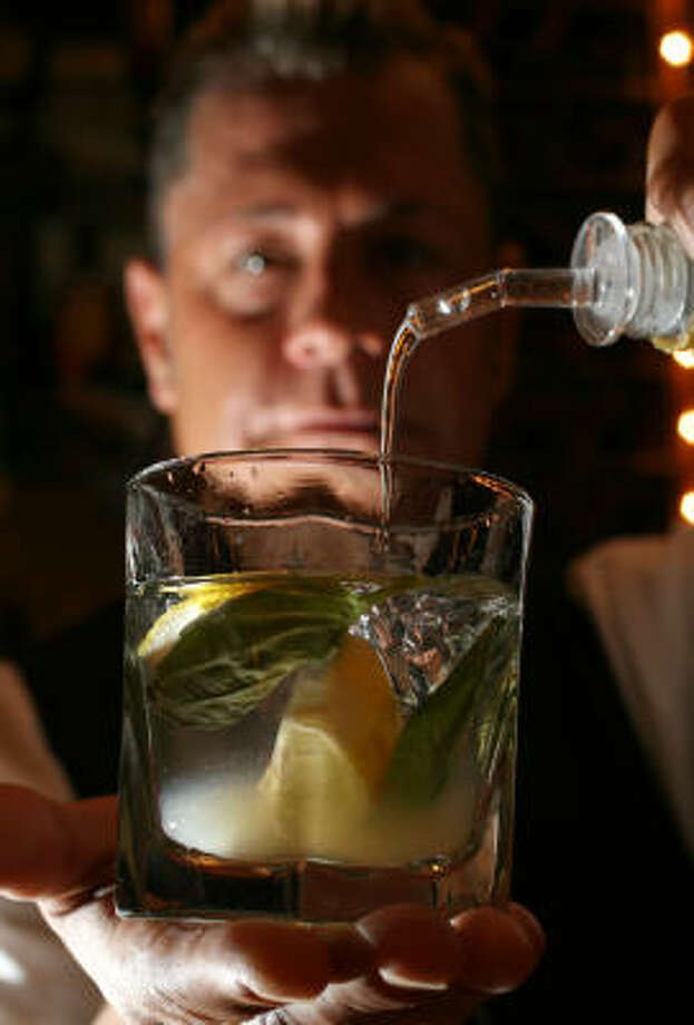 Bartender Terry Melvyn mixes a Basil and Brown Sugar Mojito at Ouisie's Table. Photo: SHARON STEINMANN:, CHRONICLE