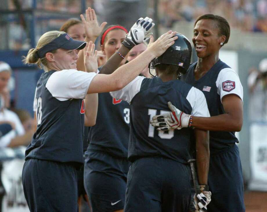 United States' Michelle Moultrie (#15), center, is greeted by her teammates after scoring against Japan in the first inning of a World Cup of Softball game in Oklahoma City, Saturday, July 23, 2011. (AP Photo/Sue Ogrocki) Photo: Sue Ogrocki, STF / AP