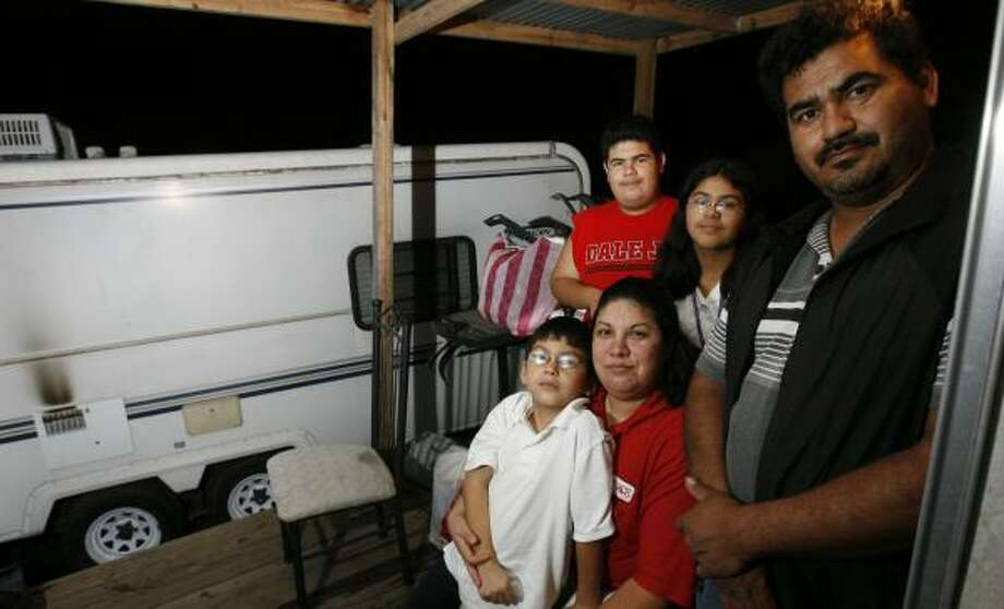 Hector and Patricia Orozco and their children — Hector, 13; Xena, 11; and Jesus, 8 — are living in a borrowed trailer after their mobile home was damaged by Hurricane Ike. Photo: SHARON STEINMANN, CHRONICLE