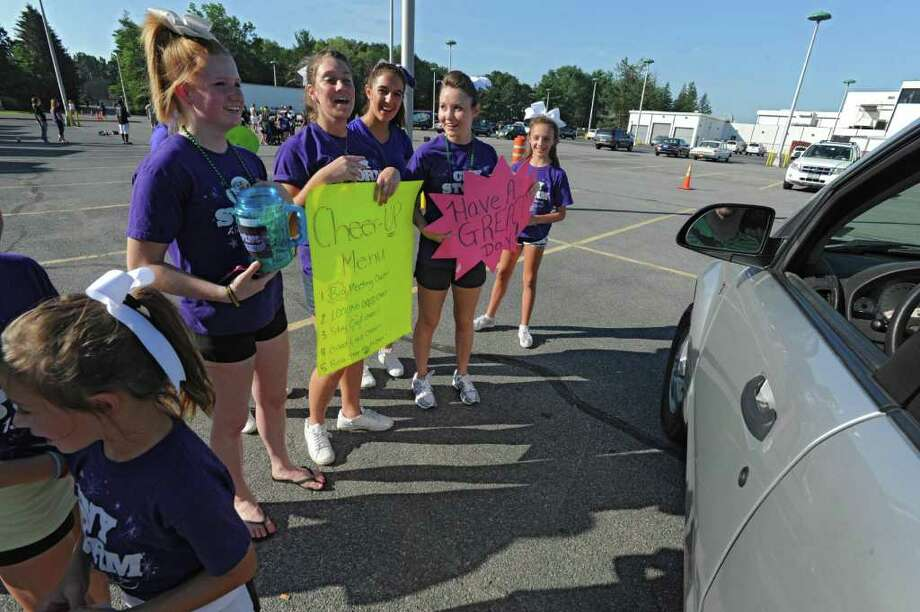 Members of the local branch of the CNY Cheer Team, a statewide cheerleading group, do a cheer for a drive-through donator at the Times Union parking lot in Colonie, N.Y. Friday, July 22, 2011. The Cheer Up event raised money for the traveling team. The event was sponsored by FLY Morning Rush (92.3 FM) and the Times Union's On the Edge blog. (Lori Van Buren / Times Union) Photo: Lori Van Buren