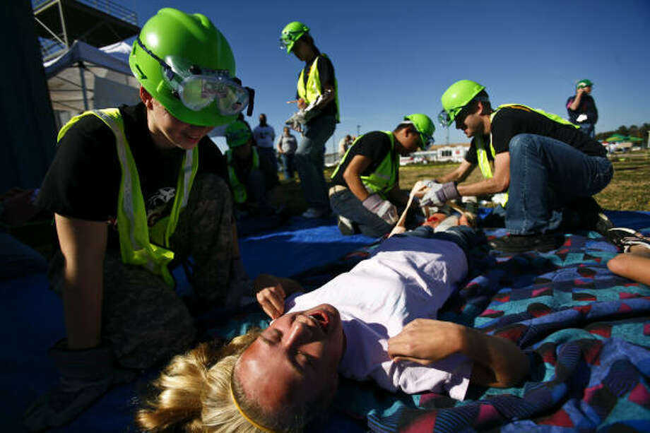 Meghan Sloan, 13, center, plays an injured patient as she receives treatment from Kelsey Devers, 16, during a disaster training drill during the Harris County Citizen Corps Community Emergency Response Team Rodeo competition Saturday in Humble.  Photo: Michael Paulsen, Chronicle