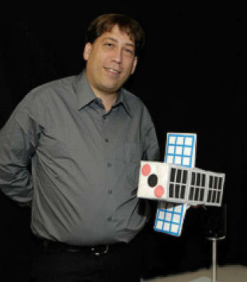 Principal researcher Doug Rowland displays a model of the compact satellite. Photo: NASA