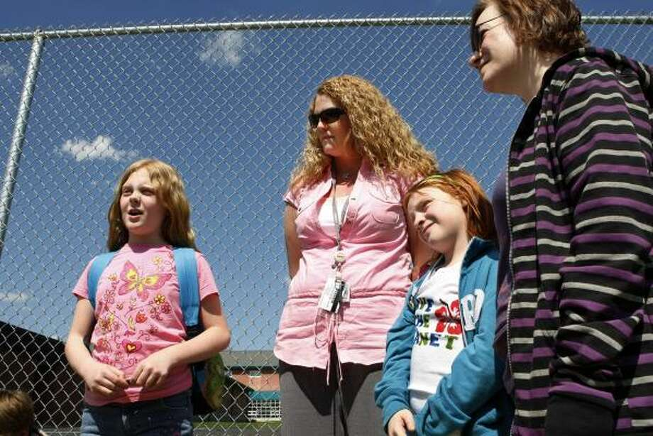 "Third-grader Elizabeth Heisler, left, won't get to wear her ""can-can"" dress after an uproar over a Women's History Month program at Maude Wilkins Elementary School in Maple Shade, N.J. Her mother, Andrea Heisler, center, spoke about the controversy Wednesday with Connie Fisher and her fourth-grade daughter Braelyn Fisher. Photo: Mel Evans, AP"