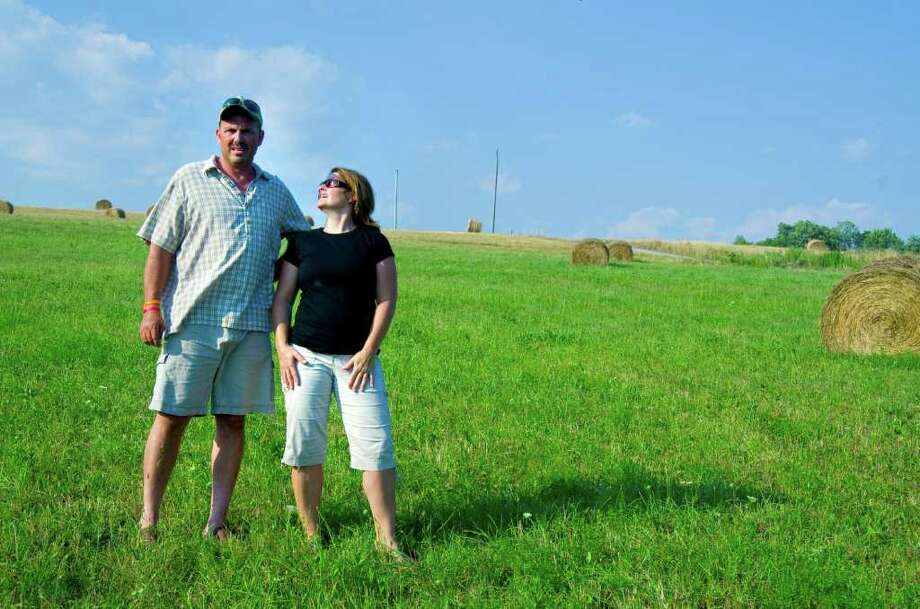 In this July 17, 2011 photo, Dave and Karen Beinlich are shown on their farm near Forksville, Pa. The Beinlichs are among thousands of residents living atop the Marcellus Shale who signed lowball leases in the years leading up to the gas boom in Pennsylvania. (AP Photo/Ralph Wilson) Photo: Ralph Wilson