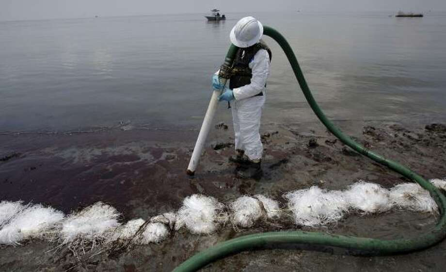 While efforts to deal with surging oil continue Wednesday out in the Gulf, cleanup work on shore — as in Belle Terre, La. — mainly depends on individuals wielding suction hose. Photo: Eric Gay, Associated Press