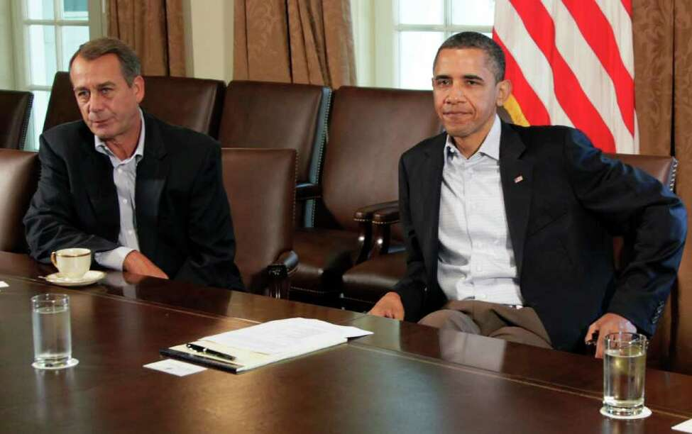 President Barack Obama sits next to House Speaker John Boehner of Ohio, left, in the Cabinet Room of the White House, Saturday, July 23, 2011, in Washington, as they meet to discuss the debt. (AP Photo/Carolyn Kaster)