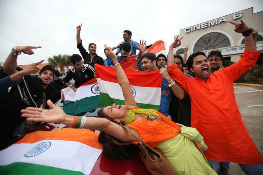 Rekha Gajjar, center, joins in celebrating India's win over Pakistan during the semifinal of the Cricket World Cup on Wednesday at a watching party at the Bollywood Cinema 6 in Sugar Land. Photo: Mayra Beltran, Chronicle