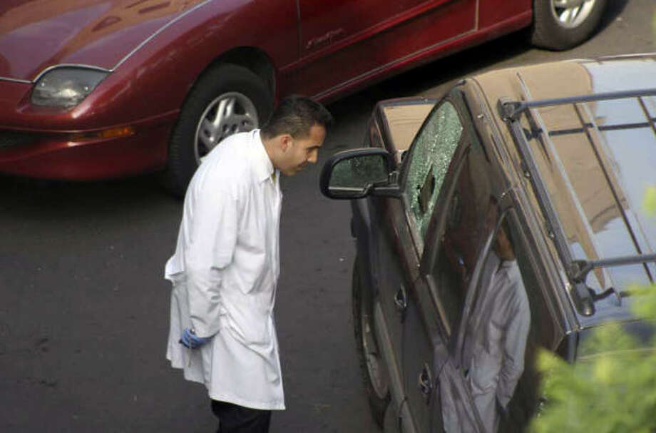 A police forensic expert examines the vehicle of Jose Nemesio Lugo after he was shot dead by unknown gunmen in Mexico City, Monday. Lugo, who was a high-ranking intelligence official in charge of investigating drug and migrant smuggling, among other issues, was shot while he was driving to work, said a spokesman at the city prosecutor's office. Photo: AP
