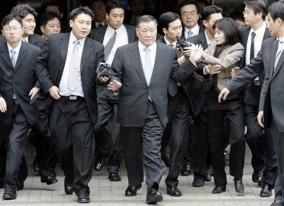 Hyundai Motor Co. Chairman Chung Mong-koo breaks away from reporters after leaving court on Monday in Seoul, South Korea. Chung, convicted on embezzlement and other charges, is free pending appeal. Photo: LEE JIN-MAN, ASSOCIATED PRESS